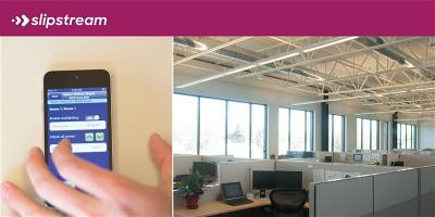 networked lighting controls app on mobile device next to office space lighting